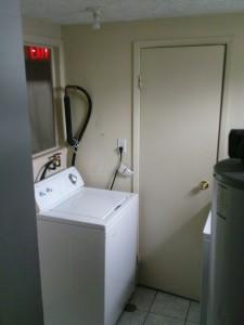 Waschküche mit Blick auf die Waschmaschine. Hinter der Tür ist das zweite Bad.