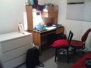 Schreibtisch und Kommode mit Klamotten