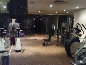 Fitnessraum mit Squash Court im Hintergrund (dunkel)