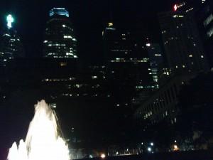 Skyline bei Nacht, mit beleuchtetem Brunnen im Vordergrund.